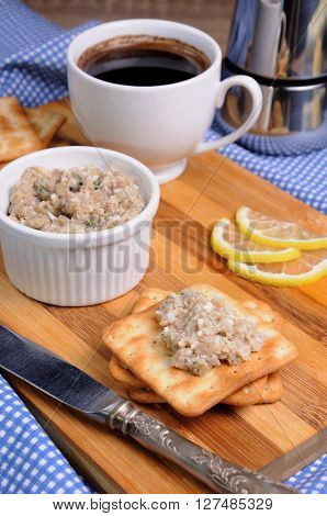 Snack of fish paste (forshmak) on a cracker with a cup of coffee