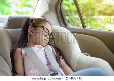a little girl sleeping in the carseat