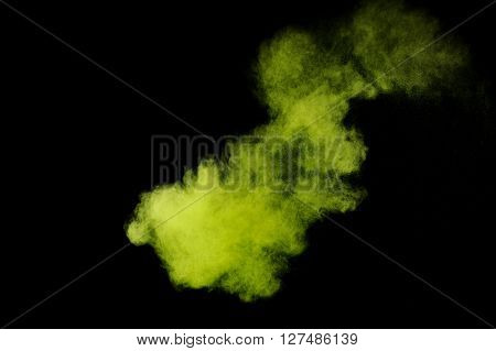 Abstract green powder explosion on black background. Paint Holi.