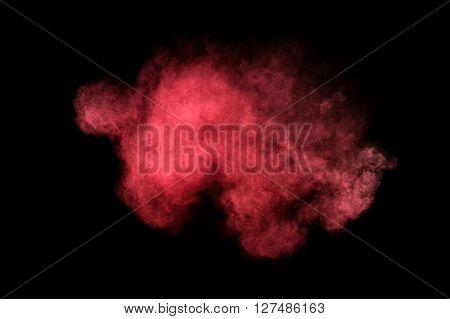 Abstract red and pink powder explosion on black background. Paint Holi.