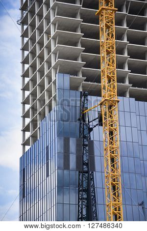 Yellow Crane On Skyscraper Construction Site With Windows Reflecting Sky
