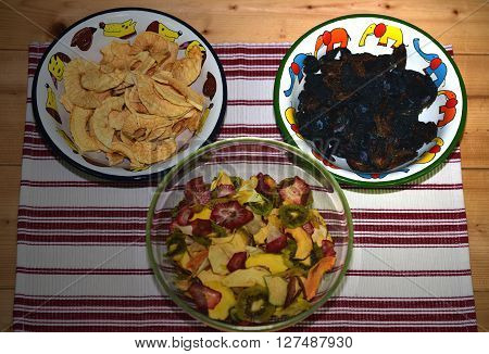 Dried fruit in glass and metallic dishes on wooden ground