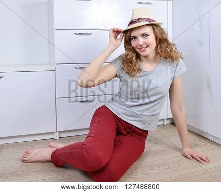 Emotional happy young woman sitting on the floor in a summer yellow hat.