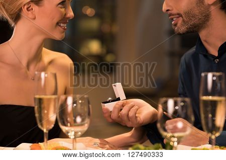 Man holding box with solitaire ring making marriage propose to his girlfriend. Young handsome husband gifting a ring to wife on anniversary. Man asking marry to his happy girlfriend