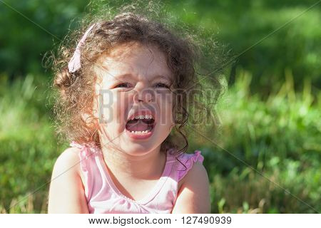 Photo of crying baby girl outdoors closeup