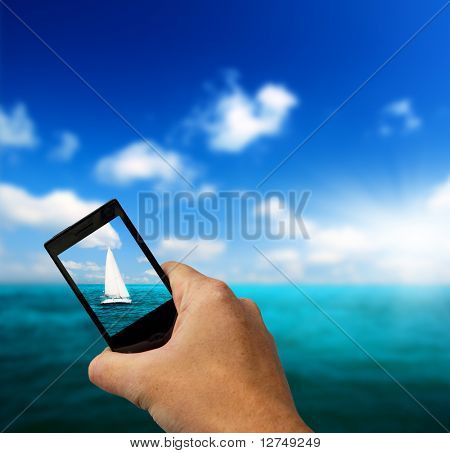 Segelboot-Himmel und Handy in der hand