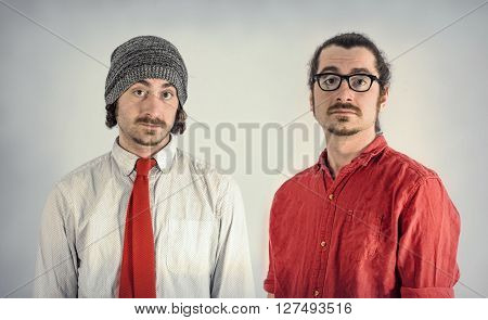 Twin adult men with beards take serious portrait