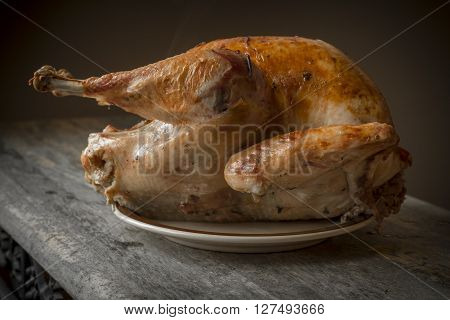 Country roasted turkey with crispy skin on rustic wooden table