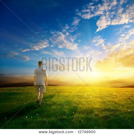 one man and field of spring grass and sunset