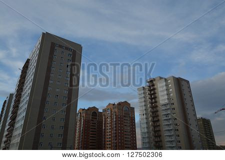 Multistoried, new and stylish living blocks of flats. Real estate. New houses and blue sky with clouds. Newly built blocks of modern flats. Modern and new apartment buildings. Photo is made in Krasnoyarsk, Siberia, Russia.