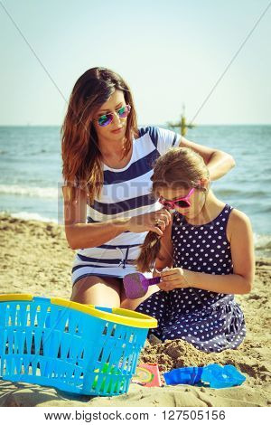 Family mother and daughter having fun on beach. Parent mom and child kid digging hole in sand. Summer vacation holidays relax.