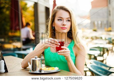 Beautiful Woman Drinking Tea in a Cafe Outdoors. Summer City Background. Shallow Depth of Field. Toned Photo.