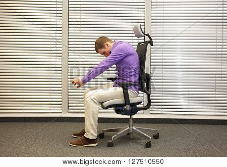 man exercising on chair in office, healthy lifestyle -profile
