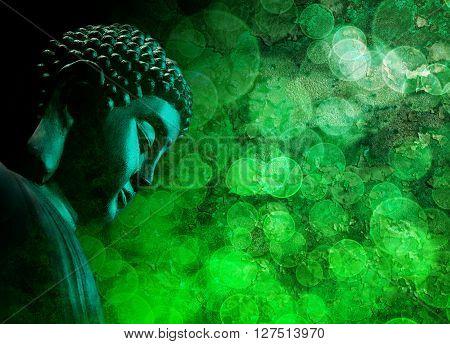Bronze Zen Buddha Statue Meditating with Blurred Textured Green Background
