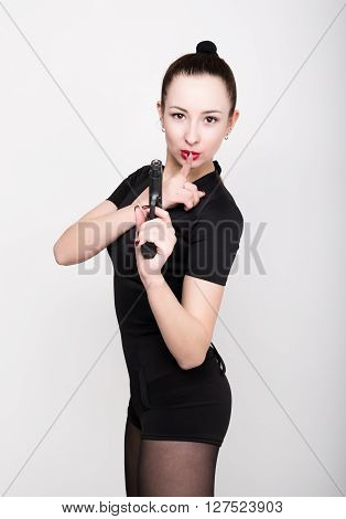 leggy slim beautiful sexy girl in lacy lingerie on a high heels,  holding gun, raised his index finger to his lips, posing.