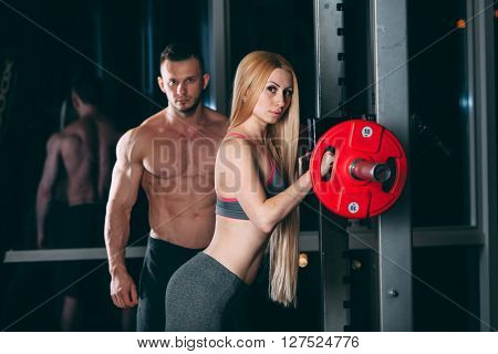 Young couple exercising in gym with weights the man seems to be the personal trainer.