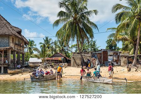 Ambatozavavy Nosy Be Madagascar - December 19 2015: Tourists take places on their traditional wood pirogue with outrigger in the Ambatozavavy village on the island of Nosy Be Madagascar. Traditional fishing village on Nosy Be island with wooden dugout row