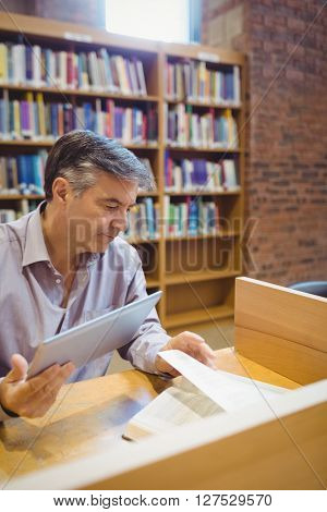 Professor sitting at desk holding digital tablet and reading book in college library