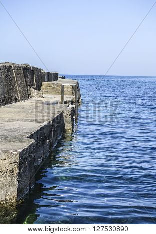 Vertical photo of water from the Mediterranean and concrete breakwater. Metal ladder mounted breakwater. Strong and gentle concept.