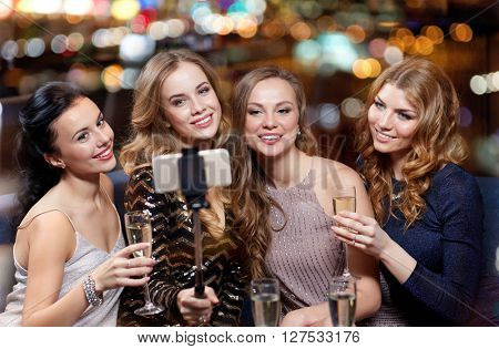 celebration, friends, bachelorette party, technology and holidays concept - happy women with champagne and smartphone selfie stick taking picture at night club