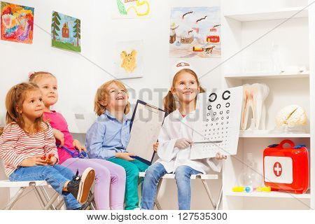 Happy little oculist and patients sitting at the doctor's room