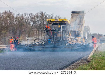CZECH REPUBLIC, PLZEN, 10 APRIL,2016:Worker operating asphalt paver machine during road construction and repairing works