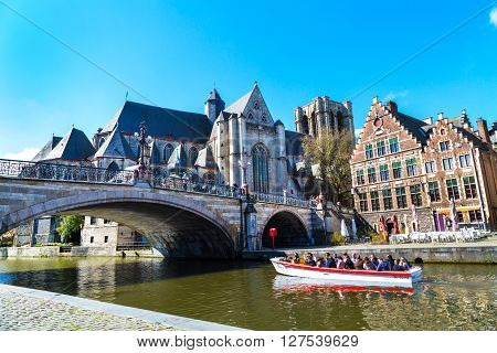 Ghent, Belgium - April 12, 2016: Medieval St. Michael Bridge, church, canal and boat with tourists in Ghent, Belgium