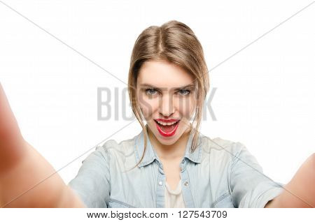 Closeup of beautiful playful woman making selfie photo on isolated white background and looking at camera