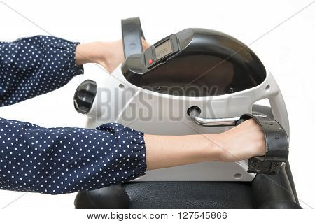 Woman exercising on exercise bike Upper / Lower body rehab hand cycle