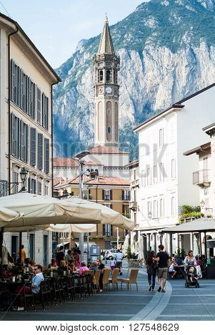 Lecco, Italy - September 1st 2015: People enjoying themselves in Piazza XX Settembre on September 1st 2015 in Lecco Italy with Basilica of Saint Nicholas (Campanile di San Nicol