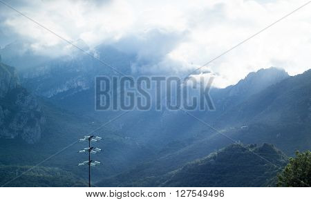 dramatic light falling from the sky in Italy with a shiny utility pole in the foreground