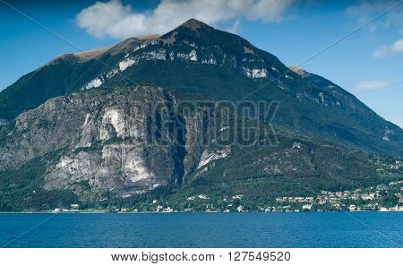a lush and sunny mountainous view (possibly Menaggio) from the town of Varenna near Lake Como in Italy