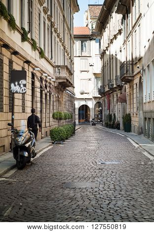 Milan, Italy - September 5th 2015: a man walking down a quaint street in central Milan.