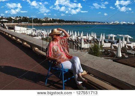 CANNES FRANCE - JULY 5 2015. Woman relaxing in chair on Croisette promenade in Cannes France. Cannes located in the French Riviera. The city is famous for its Film Festival. CANNES FRANCE - JULY 5 2015: