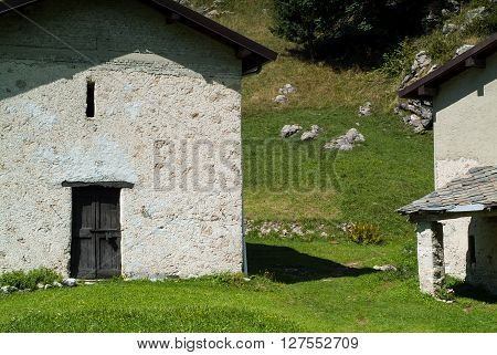 photo of a sunlit traditional house at Piani d'Erna (part of the Alps) near Lake Como in Italy
