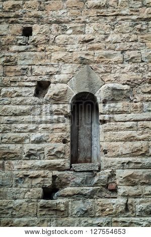 closeup photo of a narrow window on a stone wall in Italy