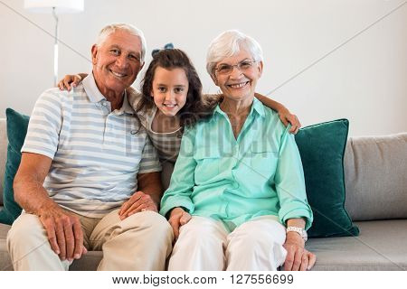 Portrait of grandmother and grand father with their granddaughter sitting on sofa in living room