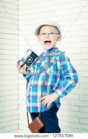 Little boy in a cap with retro camera. Stands and shouts