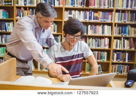 Professor assisting a student with laptop in college library