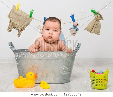 little two-month girl bathes in a  trough and dry her clothes