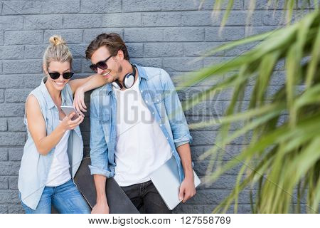 Young couple leaning against wall using mobile phone