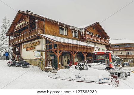 Poiana Brasov Romania - February 5 2016: Postavaru chalet and snow covered snowplow tractor at 1604m altitude in Postavaru mountain Poiana Brasov winter resort Brasov county.