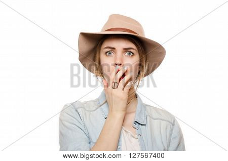 Confused pretty woman in hat look at camera touching her face