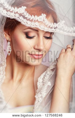 Portrait of a beautiful woman in a wedding dress in the image of the bride. Wedding. Young Gentle Quiet Bride in Classic White Veil. Portrait of beautiful bride. Wedding dress. Wedding decoration