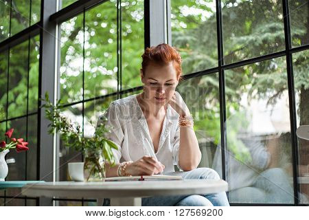 Portrait of a charming youn girl who sits and wrote in a notebook