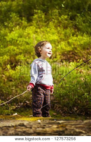 A Little Boy Playing In The Woods.