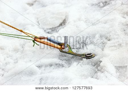 Ice Piton Screwed into Ice with Belaying Ropes and Carabiner Safety Mountain Climbing Gear Used on Glacier Snow Close Up