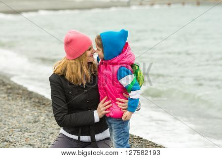Little Girl And Her Mother Touching Noses On The Beach In Cold Weather