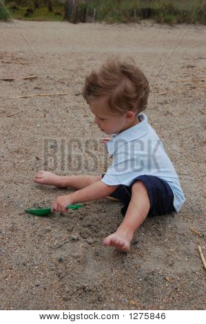 Little Boy Digging In The Sand