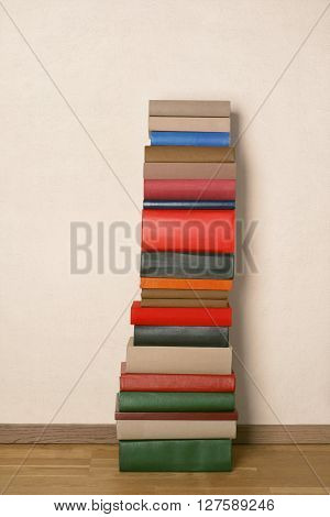 Old colorful books on wooden floor near the white wall